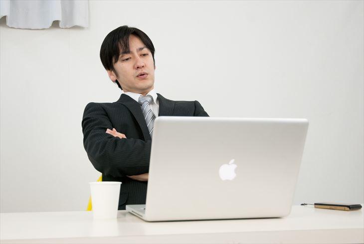 パソコンの前で困っている男性
