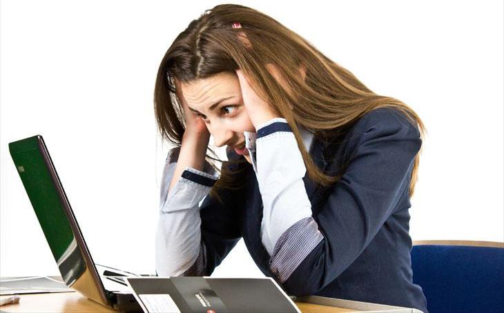 パソコンの前で頭をかかえる女性